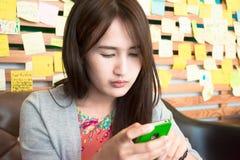 Muchacha que juega smartphone Imagen de archivo