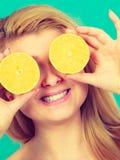 Muchacha que la cubre ojos con los agrios del limón Foto de archivo libre de regalías