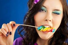 Muchacha que lame el lollipop Imagenes de archivo