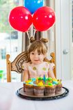 Muchacha que lame los labios en Front Of Birthday Cake Foto de archivo libre de regalías