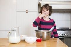 Muchacha que lame talud mientras que prepara la magdalena Imagen de archivo