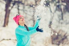 Muchacha que lanza nieve alrededor Fotografía de archivo