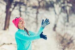 Muchacha que lanza nieve alrededor Imagenes de archivo