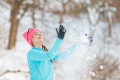 Muchacha que lanza nieve alrededor Foto de archivo