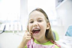 Muchacha que le muestra los dientes de leche sanos en la oficina dental Fotos de archivo libres de regalías