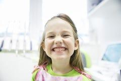 Muchacha que le muestra los dientes de leche sanos en la oficina dental Imágenes de archivo libres de regalías