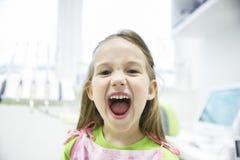 Muchacha que le muestra los dientes de leche sanos en la oficina dental Fotografía de archivo