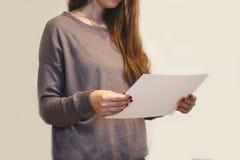 Muchacha que lee el folleto blanco en blanco del folleto del aviador A4 Pres del prospecto Fotos de archivo libres de regalías