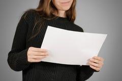 Muchacha que lee el folleto en blanco del folleto del aviador del blanco A4 Pres del prospecto Fotos de archivo libres de regalías
