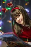 Muchacha que lee el libro de la Navidad foto de archivo libre de regalías