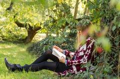 Muchacha que lee el libro en el parque Foto de archivo