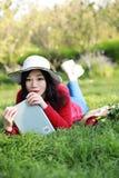 Muchacha que lee el libro mujer joven hermosa con el libro que miente en la hierba outdoor Día asoleado fotos de archivo