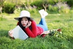 Muchacha que lee el libro mujer joven hermosa con el libro que miente en la hierba outdoor Día asoleado fotos de archivo libres de regalías
