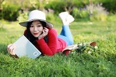 Muchacha que lee el libro Mujer joven hermosa rubia con el libro que miente en la hierba outdoor Día asoleado imágenes de archivo libres de regalías