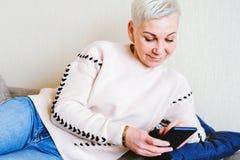 Muchacha que lee SMS en el smartphone La emoci?n de la sorpresa alegre El corte de pelo corto de las mujeres Perfil elegante de m fotografía de archivo
