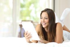 Muchacha que lee un ebook en la cama Imagen de archivo