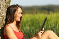 Muchacha que lee un ebook o una tableta en un campo verde Imagenes de archivo