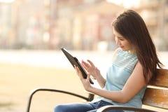 Muchacha que lee un ebook o una tableta en un parque Imagen de archivo libre de regalías