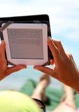 Muchacha que lee un ebook que miente en ociosos del sol en la playa Fotografía de archivo