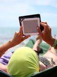 Muchacha que lee un ebook que miente en ociosos del sol en la playa Imagenes de archivo