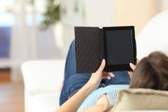 Muchacha que lee un ebook y que muestra la pantalla Fotos de archivo