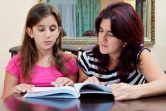 Muchacha que lee un libro con su madre hermosa Imagenes de archivo