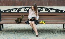Muchacha que lee un libro con un gato en un banco en la ciudad Imágenes de archivo libres de regalías