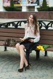 Muchacha que lee un libro con un gato en un banco en la ciudad Foto de archivo
