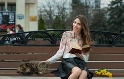 Muchacha que lee un libro con un gato en un banco en la ciudad Fotos de archivo libres de regalías