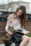 Muchacha que lee un libro con un gato en un banco en la ciudad Foto de archivo libre de regalías