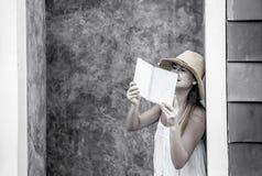 Muchacha que lee un libro contra una pared en la calle Fotos de archivo libres de regalías