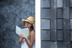 Muchacha que lee un libro contra una pared en la calle Foto de archivo libre de regalías
