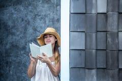 Muchacha que lee un libro contra una pared en la calle Imágenes de archivo libres de regalías