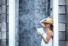 Muchacha que lee un libro contra una pared en la calle Imagen de archivo