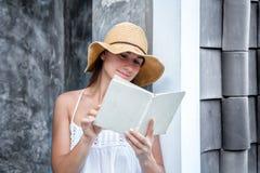 Muchacha que lee un libro contra una pared en la calle Foto de archivo