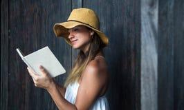 Muchacha que lee un libro contra una pared en la calle Fotografía de archivo
