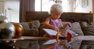 Muchacha que lee un libro de la historia en la sala de estar 4k almacen de metraje de vídeo