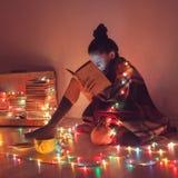 Muchacha que lee un libro debajo de la manta en casa Fotos de archivo libres de regalías