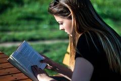 Muchacha que lee un libro en día de primavera soleado en el parque en un banco Imagen de archivo libre de regalías