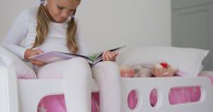 Muchacha que lee un libro en dormitorio en el hogar cómodo 4k metrajes