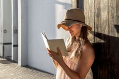 Muchacha que lee un libro en el amanecer Imagenes de archivo
