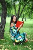 Muchacha que lee un libro en el parque Fotografía de archivo