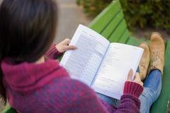 Muchacha que lee un libro en el parque Foto de archivo libre de regalías