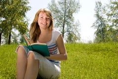 Muchacha que lee un libro en el parque Fotos de archivo