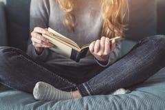 Muchacha que lee un libro en el sofá Imagen de archivo