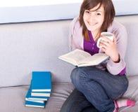 Muchacha que lee un libro en el sofá Fotos de archivo