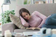 Muchacha que lee un libro en el sofá Foto de archivo