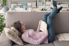 Muchacha que lee un libro en el sofá Imagen de archivo libre de regalías