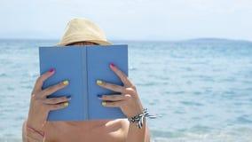 Muchacha que lee un libro en el sombrero de paja de la playa que lleva Imagenes de archivo