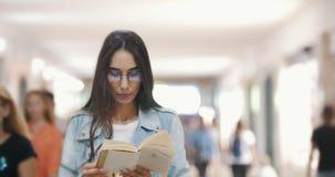 Muchacha que lee un libro en el subterráneo en el medio de la muchedumbre almacen de video
